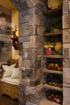 love the stone walls and built in shelves in this kitchen