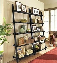 We have shelves similar to these in our family room.  We purchased ours from  The Storehouse at Hyde Park in Tampa, Fl when they were located there.  I love how versatile and simple they are.  You can incorporate them into almost any style of home and in pretty much in any room.  These are Crate and Barrel leaning shelves.