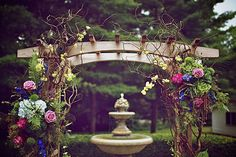 Gorgeous arch with ferns and peacock feathers.