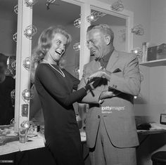 High-voltage smiles brighten the scene backstage at the Dunes Hotel in Las Vegas, Nevada, as singer-actress comedian George Burns. The veteran showman discovered the sultry Swedish entertainer at the hotel years ago and, today, she's an established movie star.