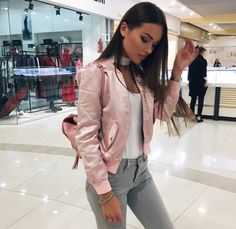 Pretty brunette. Light pink silk bomber jacket with jeans. Winged eyeliner.