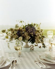 Centerpieces made from hydrangeas, dogwood, spirea, roses, and fern placed in footed vessels