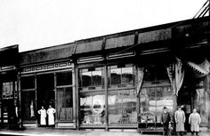 Exterior view of the Barnes' grocery store on First Street in Snohomish, Washington. The Bruhn and Henry Butcher's shop is on the left. The proprietors of both shops stand in front of their buildings, ca 1900. When Barnes Grocery burned down in a 1911 fire, stacks of flour fell into the basement. Once the building cooled down, Barnes was cleaning up the flour when he found a pocketbook with $950 dollars inside.