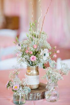 Rustic wedding centerpiece idea -baby's breath + pink flowers in gold mason jars on tree slice {Katelyn James Photography}