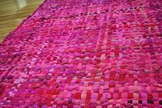Remember those pot-holder looms? Think much bigger! Artist/crafter Crispina ffrench took the idea and scaled it UP. She uses a giant loom to weave cotton tee shirts or wool sweaters in the very same way, to make thick, dramatic rugs