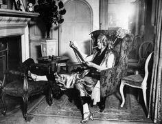 A lady wearing a smoking suit, reading a newspaper by the fireplace, 1922. (Photo by Firmin/Getty Images