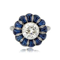 This Diamond and Sapphire Cabochon Ring has a brilliant round cut diamond, is surrounded by cabochon Ceylon sapphires.