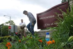Ames Noon Lions Club members Kate Mason, kneeling, and Don Schaffer, standing left, and Jim Gunning, standing in background, work on the club's flower garden near the entrance to Brookside Park on Wednesday. Photo by Michael Crumb/Ames Tribune