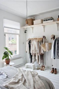 Love this minimalist and feminine Scandinavian styled bedroom with painted white wood floors, white clothing racks, Roman blinds, bracket-mounted unfinished wood shelves, and decor and furniture in all-white and neutral hies!