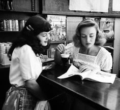 Actress Donna Reed looking at a magazine with a soda-fountain attendant. Photo by Bob Landry, 1946.