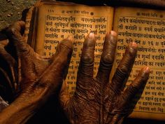 Hands move across a classic Hindi text