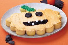"""Jack-o'-Lantern """"Cake"""":  Arrange cupcakes on large platter to resemble a stemmed pumpkin as shown; frost. Use colored sugar to fill in the stem. Add 2 cookies for the jack-o'-lantern's eyes. Crush more cookies & sprinkle over cake for the mouth. Arrange mini marshmallows in mouth for the teeth."""