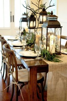"""Chic Thanksgiving Tablescape Inspiration.   """"Lighten up your dinner table with towering candle lanterns-- a winter-inspired bonus when decorated with pine."""""""