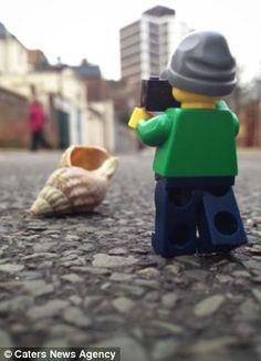 The lego man takes a photo of a seashell out of its usual beach context
