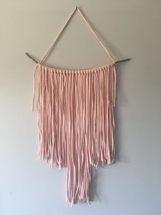 macramé wall hanging made with woolandthegang t-shirt yarn (in pink 'nude lips') and a dried branch nursery kids bedroom decor trend