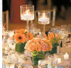 Centerpieces were kept simple: Each table had three different square vases filled with orange blossoms and two tall glass pedestals with floating candles.