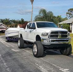 Lifted white Dodge Ram 2500 cummins diesel chrome wheels towing pulling boat