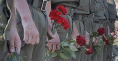 20150902 - Soldados ucranianos seguram flores durante o funeral do também soldado da Guarda Nacional Igor Derbin, que foi morto em um confronto na segunda-feira (1º), em uma base militar em Novi Petrivtsi, na Ucrânia. A polícia disse que 141 pessoas permanecem hospitalizadas após um protesto nacionalista em Kiev. Além de Igor, outros dois oficiais também morreram. PICTURE: Efrem Lukatsky / AP