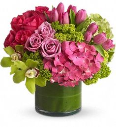 Green and pink hydrangeas, green cymbidium orchids, hot pink and lavender roses, tulips and more are beautifully arranged in a large clear glass cylinder vase.
