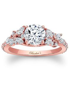 An exquisite diamond engagement ring, featuring a rose gold shank with shared-prongs set diamonds flanking the prong-set round diamond center. The cathedral shoulders are adorned with marquise cut diamonds artfully arranged, while small round diamonds accent the shoulders for an elegant touch of glam. Price excludes center stone