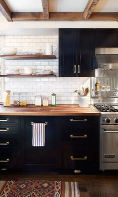 A beautiful kitchen. Subway tiles, black cabinets, butcher block counters, and open shelving! Love the warmth of it all.:
