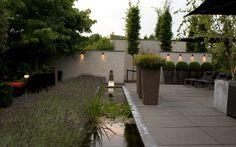 Avondbeeld/Sfeerbeeld van de achtertuin met de op de muren geplaatste verlichtingsarmaturen. De randafwerking van de lange vijver is uitgevoerd in lood.