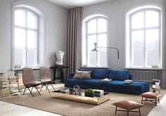 Navy sofa in neutral living room with high ceilings and brown furniture