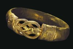 Greek Gold Heracles Knot Bracelet, C. 300 BCFormed from a hollow hoop fashioned from sheet, convex on the exterior, each end with a collar terminal secured by a pin, its tip with granulation, the collars each with twisted wire filigree palmettes...