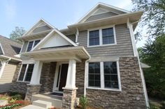 Exterior stone and vinyl siding. Column detail with stone base. Paneled front door with sidelites. Single-hung double windows.