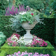 Flower filled Stone Urn in a formal garden with a boxwood hedge.  Traditional garden Style.  Luxury Living.