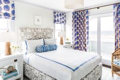 Gorgeous bedroom boasts a gray ikat upholstered bed dressed in white and blue hotel bedding as well as a blue tie dyed bolster pillow flanked by white lacquered nightstands and tapered wood lamps tucked below windows dressed in purple and blue block print roman shades.