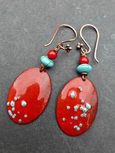 Torch-fired enameled copper metal and glass with stone and copper. Suspended from handcrafted ear wires, these earrings measure about 2 inches from end to end. Earrings are lightweight. Comes beautifu