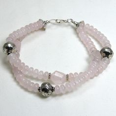 """Handmade gemstone quartz bracelet features semi-precious rose quartz rondelle gemstones, sterling silver accent beads, lobster claw clasp and wire band. 8"""" in length. Add a necklace, pendant and earri"""