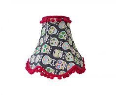 This wonderful lampshade has been traditionally hand made in the UK. The cotton fabric is hand stitched on to a ribbon binding and the wire frame beneath is powder coated to prevent rust. each shade is finished with a delightful pom pom trim.  Shade can be used as a bedside lamp or on a ceiling pendant although you may find it on the small side for a ceiling pendant.    Maximum wattage: 40 watt  Complete with converter plug for European fittings.  All lampshade frames fit the standard BC ...