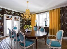 Amazing dining room features turquoise blue and brown wallpaper framing windows dressed in yellow curtains alongside an antique b=sideboard cabinet topped with peacock blue lamps.