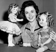 Shirley Temple was never a dolly girl either, but here she is in 1957, when she was 29 years old, posing with a 1935 Shirley Temple doll (on right) and a newer model.
