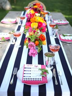 Cute way to set the table.  Nautical look with colorful flowers and accents of pink.