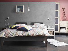 Camera da letto moderna con letto grigio, comodino e guardaroba in pino grezzo NORNÄS, biancheria da letto IKEA PS 2014.