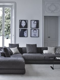 Grey sofa and black and white family portraits on the wall. Cool lounge.