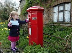 Three-year-old Jessica Farrell posts a letter in Britain's oldest postbox, in Holwell, Dorset