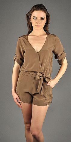 This silk romper features an overlapping v-neck bodice with concealed button and loop at chest with self tie at waist. Single button tabs at ¾ convertible sleeves and short side seam. Elastic gathers at waist.- 100% silk- Dry clean only