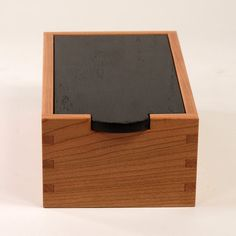 Unfigured cherry wood, box joint corners, contrasting black top.