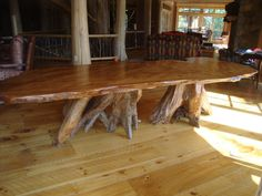 This old growth redwood rustic dining table features a 12′ long by 48″ wide by 3″ thick curly redwood slab with western cedar roots bases | Littlebranch Farm