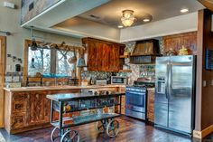 These distressed kitchen cabinets with a butcher block countertop are so cool.  The trolley I used for my island was purchased at Nebraska Furniture Mart.  The pot rack above window is galvanized pipe.
