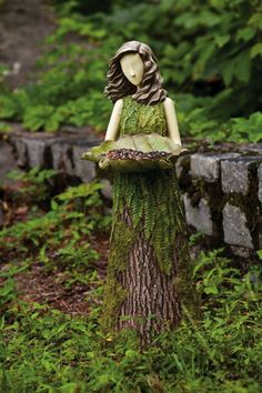 Garden fairy out of tree trunk holding bird feeder