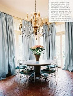 Simple, elegant dining room. Brick floors, Chivari lucite chairs with kid proof cushions in a Trina Turk outdoor fabric, an Italian antique chadelier, and fabulous drapes.