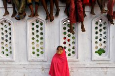 A Muslim girl looks up while some boys sit on a wall, inside the premises of a mosque, as they wait for Iftar (breaking fast) meal during the holy month of Ramadan in Chennai, India on July 16, 2014.