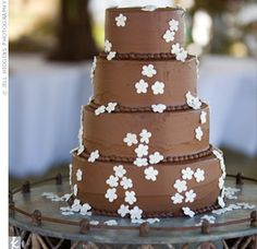 A scattering of sugar daisies that seemed to slide down the cake lent a playful touch to the rich, chocolate cake.