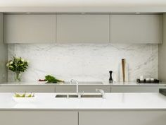 Minimalist grey kitchen design by Brayer. Handleless cabinets and white worktops