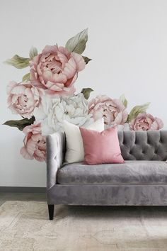 Gorgeous oversized peonies, each in different stages of bloom, designed with watercolour-textures, naturally stand-out in their soft pink and light-ivory tones. The wall decals dress-up a wall behind a silver tufted couch styled with neutral and soft-pink pillows, paired with a matching ottoman. The decals are designed for easy installation on a removable vinyl, and available in half-sized orders.